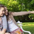 Beautiful Loving Sisters sit on a bench pointing — Stock Photo