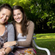 Attractive Young Sisters playfully relaxing on a park bench — Stock Photo