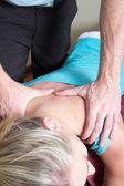 Quiropráctico ejerciendo presión sobre los hombros de la pacientes — Foto de Stock