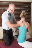 Chiropractor adjusting the female patient spine — ストック写真