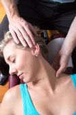 Chiropractor streching female patient neck muscles — Stockfoto