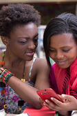 Black Female students looking on a cellphone — Stock Photo