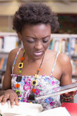 Black student using her tablet while studying — Stock Photo