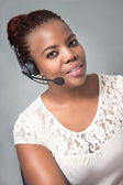 Young Black woman call center agent talking — Stock Photo