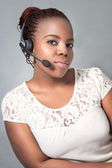 Beautiful young black call center agent talking — Stock Photo