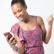Young African woman excited over text message — Stock Photo #38228291