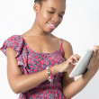 Young African American woman working on her tablet — Stock Photo #38228633