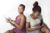 Junge freundinnen gebucht auf es tabletten — Stockfoto