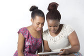 Best Friends searching the internet on tablet — Stockfoto