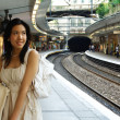 Woman waits for train - Stock Photo