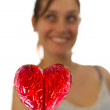 Happy young woman behind heart shaped lollipop — Stock Photo #14673013