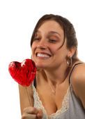 Young woman looks at heart shaped lollipop — Stock Photo