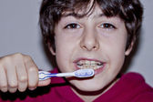 Happy teen with braces and brush his teeth — Stock Photo
