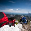 Backpack, in back mountaineer resting on the top of the hill - Stock Photo