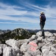 Man looks from the top of the hill on the other mountains - Stock Photo
