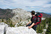 Mountaineer looks from the top of the hill on the other mountain — Stock Photo