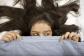 Scared girl hiding in bed — Stock Photo