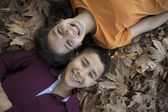 Smiling children faces in the leaves — Stock Photo