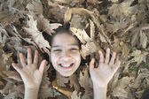 Smiling girl face and hands in the leaves — Stock Photo