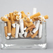 Ashtray full of cigarettes on gray background — Stock Photo