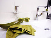 Clean bathroom sink with green towel — Stockfoto