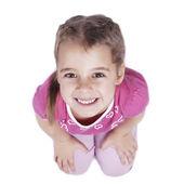 Smiling little girl sitting on the floor — Stock Photo