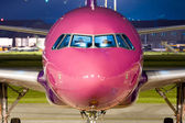 Close up of the nose of a violet airbus parked at night. — Stock Photo