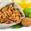 Sack of purified walnut and glass bottle of oil with green walnu — Stock Photo