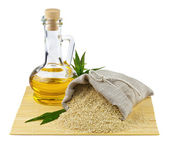 Sack of sesame seeds and glass bottle of oil — Stock Photo