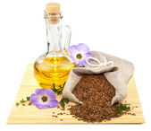 Sack of flax seeds and glass bottle of oil — Stock Photo