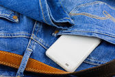 Mobile phone in back pocket of blue jeans — Stock Photo