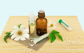 Homeopathic medication with flowers and leaves — Stock Photo