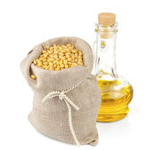 Sack of pine nuts and glass bottle of oil — Stock Photo
