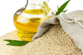 Sack of sesame seeds and glass bottle of oil on mat — Stock Photo