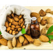 Almonds in the sack and almond oil - Stock Photo