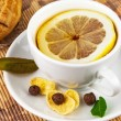 Cup of tea with lemon and cakes - Stock Photo