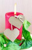 Twee papier harten en verlichte rode kaars — Stockfoto