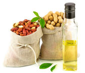 Sacks with peanut and glass bottle of oil with leaves — Stock Photo