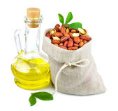 Sack of peanut and glass bottle of oil with leaves — Stock Photo
