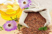Sack of flax seeds and glass bottle of oil with flowers — Stockfoto