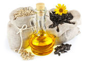 Sacks of sunflower seeds and glass bottle of oil — Stock Photo
