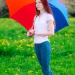 Long hair womwith colored umbrellin green meadow — Stock Photo #15344881