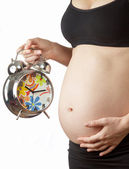 Pregnant woman belly with alarm clock — Stok fotoğraf