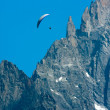 Foto de Stock  : Paraglide over Alps cliff