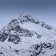 Severe mountains peaks covered by snow under dramatic sky — Stock Photo