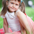 Portrait of little cute girl sitting on plaid in grass — Stock Photo