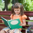 Little cute girl preschooler with book on bench in park — Stock Photo