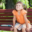 Little cute smiling girl with book on bench — Stock Photo