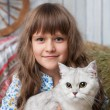 Stock Photo: Portrait of sincere girl villager with cat on hands in barn