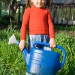 Stock Photo: Little girl with watering con vegetable garden